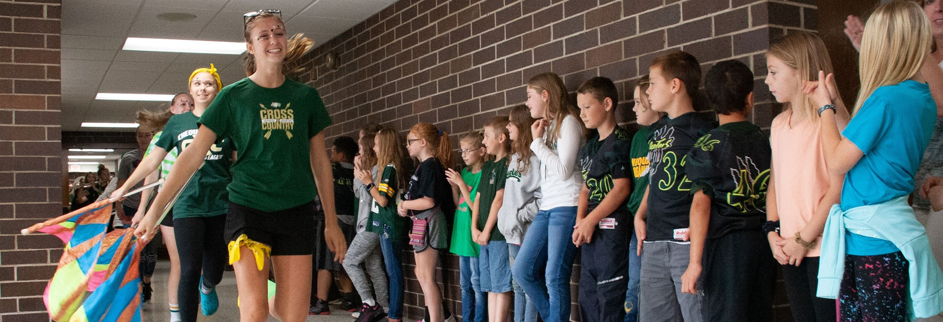 Elementary students watch the high school band tour the hallway during Homecoming
